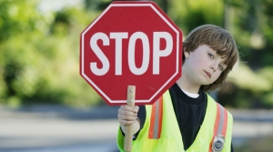 Portrait of a young boy crossing guard standing on the road holding a stop sign --- Image by © Royalty-Free/Corbis