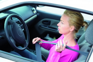Safety first. Beautiful blonde caucasian lady fastening car seat belt.
